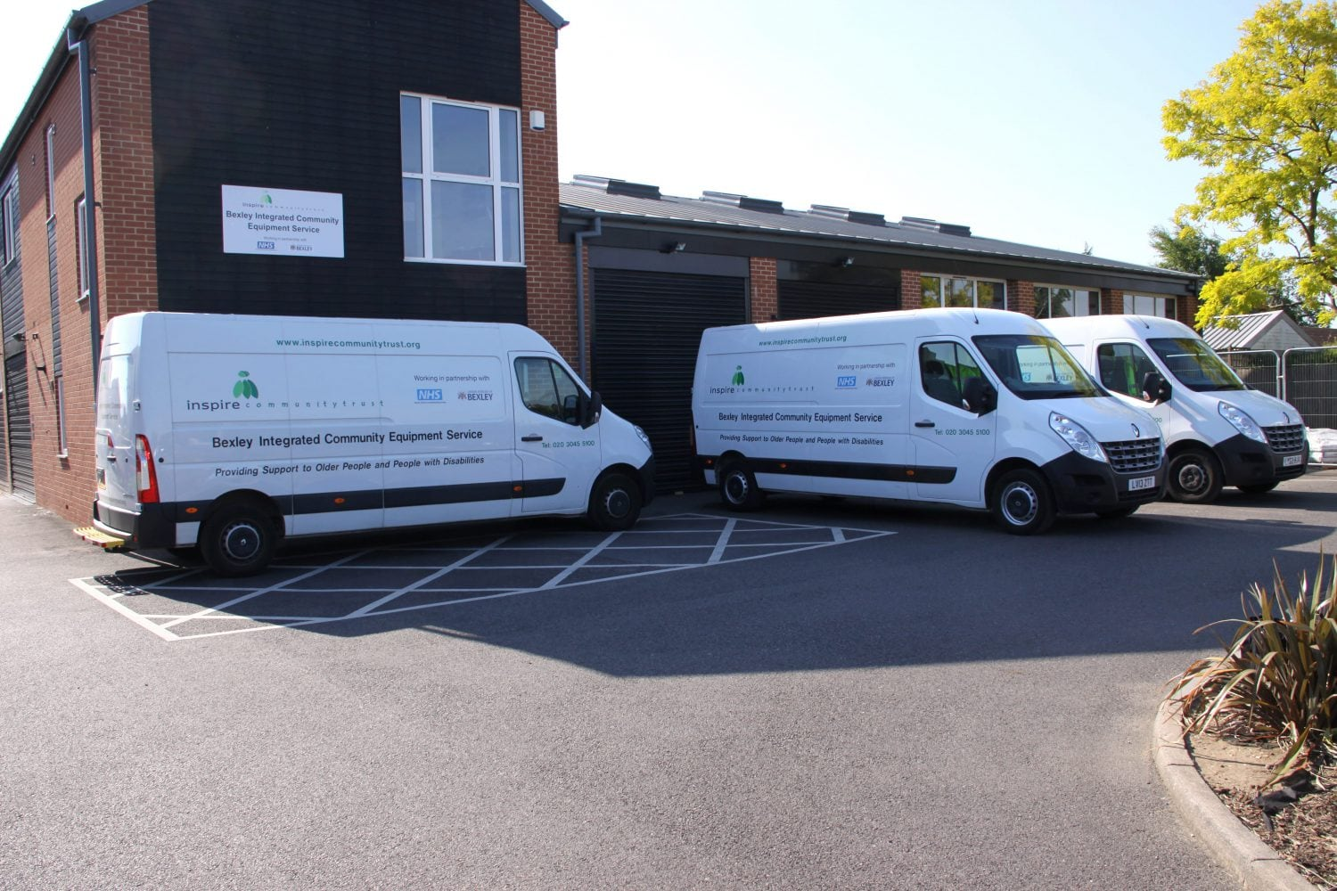 Inspire community trust vans parked outside of a building.